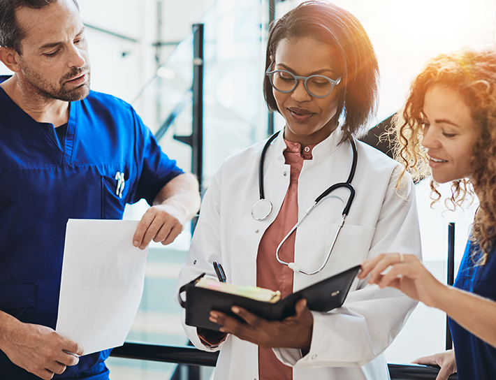woman doctor with nurses looking at file